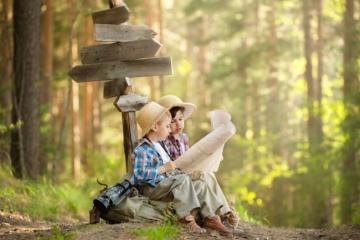 Kinder sitzen im Wald und studieren eine Karte