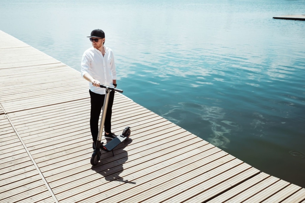 Mann mit E-Scooter am See-Steg