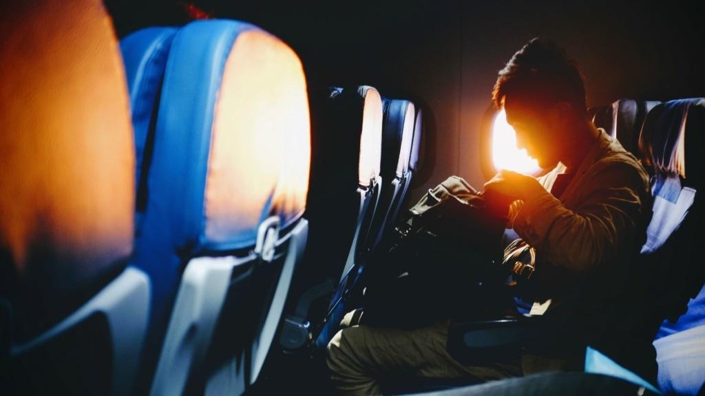 Mann sitzt im Flugzeug und durchsucht seinen Rucksack
