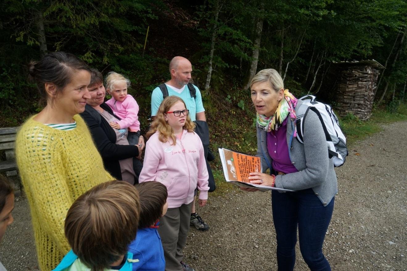 Marlies Speichern mit Buch in Hand vor Kindern beim Wandern