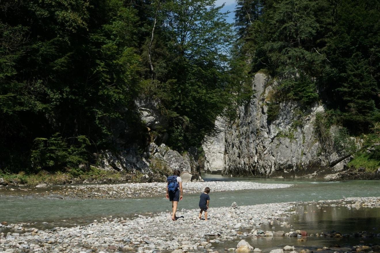 Mutter mit Kind beim Wandern am Fluss