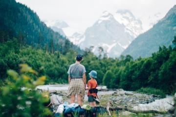 Vater und Sohn beim Wandern vor Gebirgskette