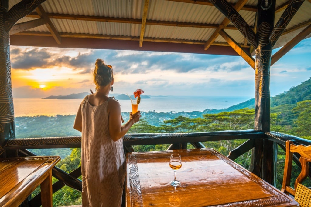 Frau mit Cocktail in der Hand auf einer Terrasse auf den Seychellen