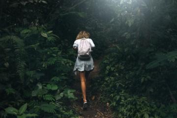 eine junge Frau mit lockigem Haar und einem Rucksack, die an einem Sommertag durch einen dunkelgrünen Tropenwald wandert.