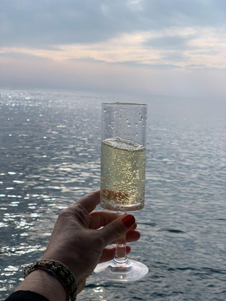 Frau hält Glas Sekt auf Yacht