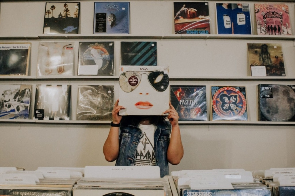 Frau hält sich im Schallplatten-Laden Cover vors Gesicht