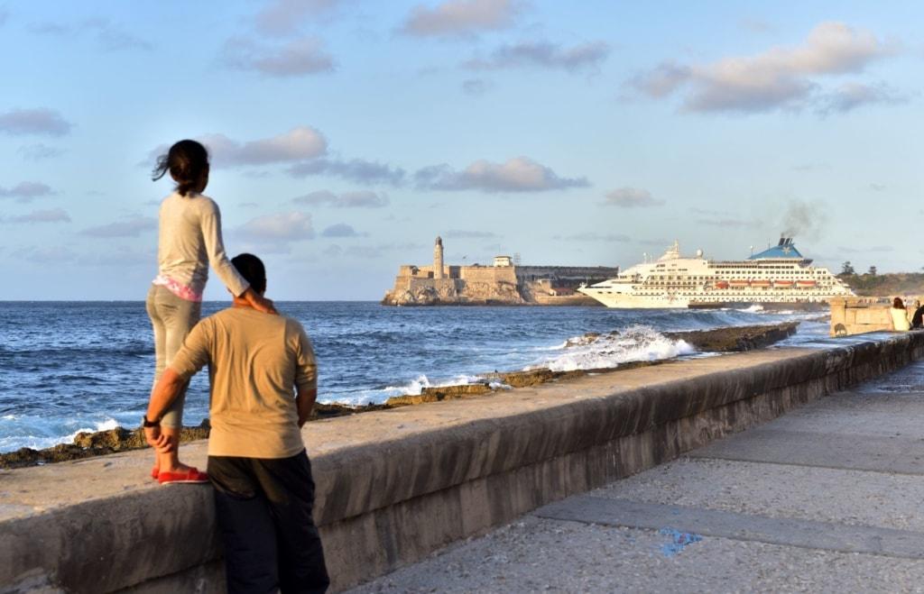 Vater und Tochter beobachten am Malecron in Havanna das Auslaufen eines Kreuzfahrtschiffes