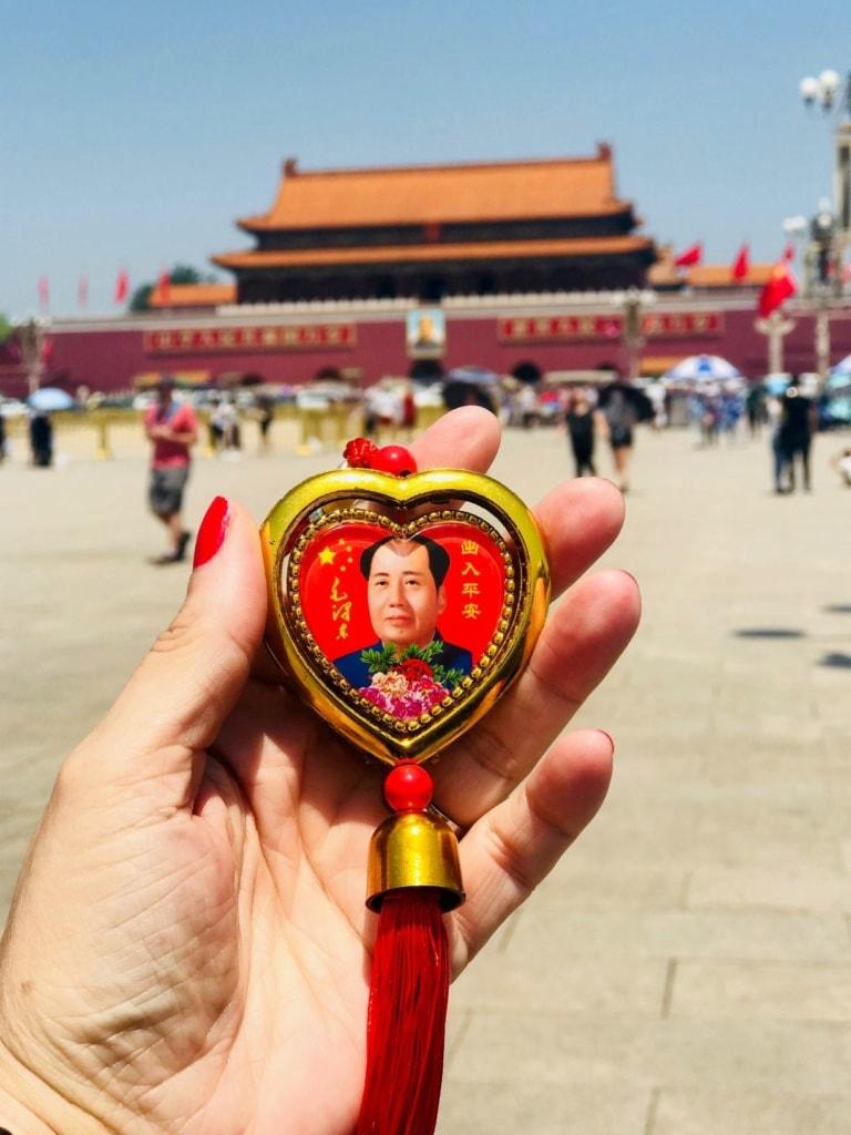 Frau hält Anhänger mit Bildnis eines Politikers in Peking in der Hand