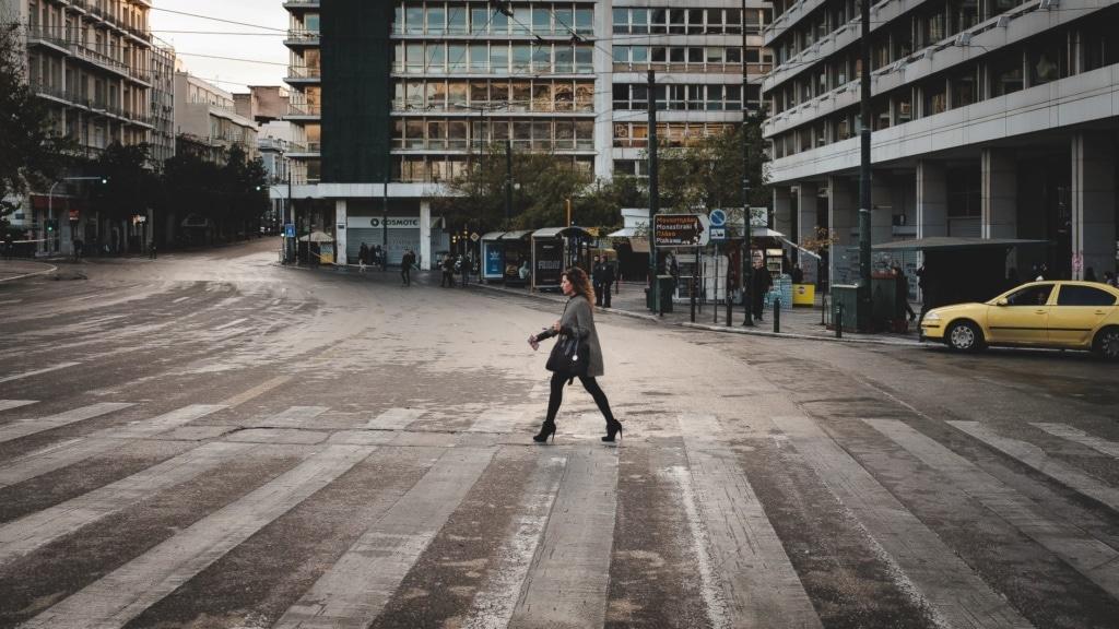 Frau überquert Zebrastreifen in Athen