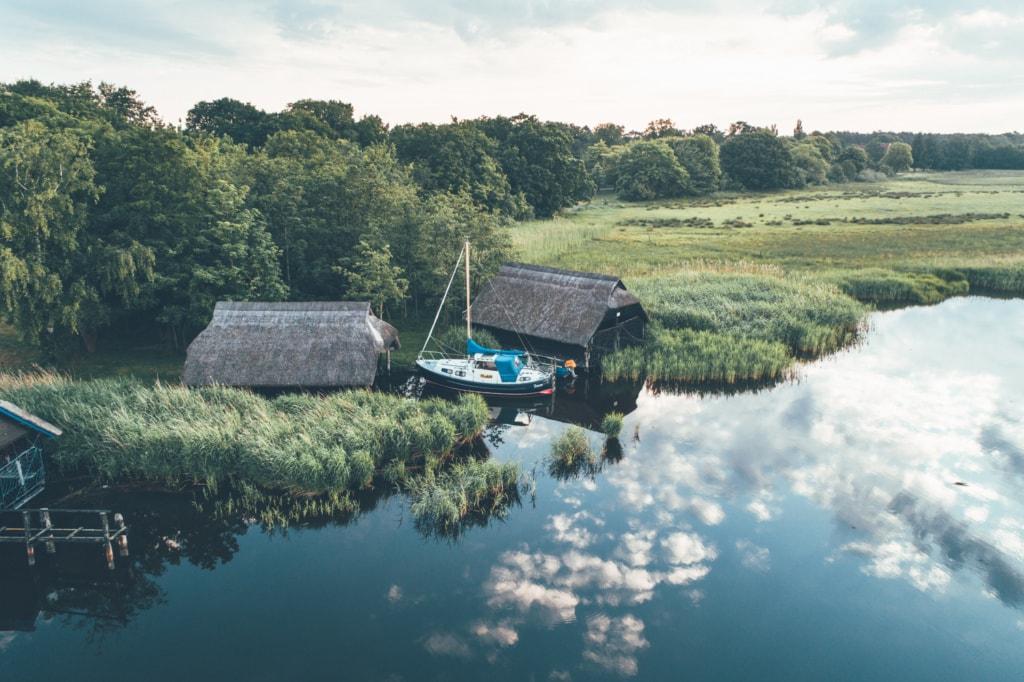 Yacht vor zwei Häusern in Seenlandschaft