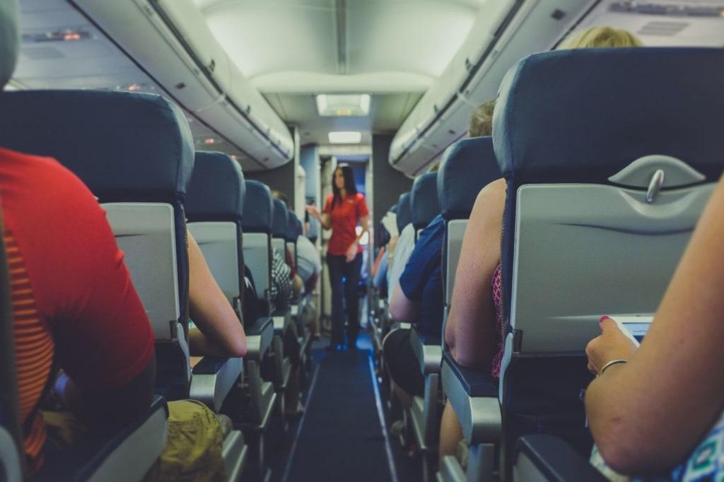 Gang im Flugzeug, Passagiere, im Hintergrund Flugbegleiterin