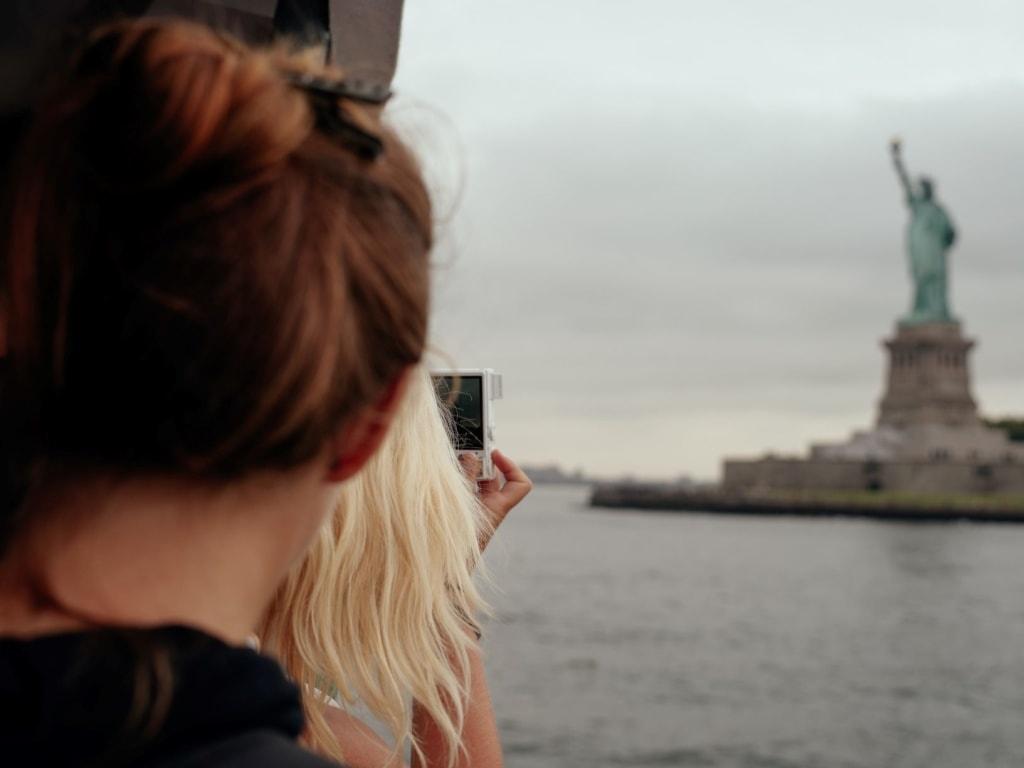 Frau fotografiert mit Handy Freihheitsstatue New York