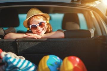 Glückliches Mädchen auf Rücksitz im Auto