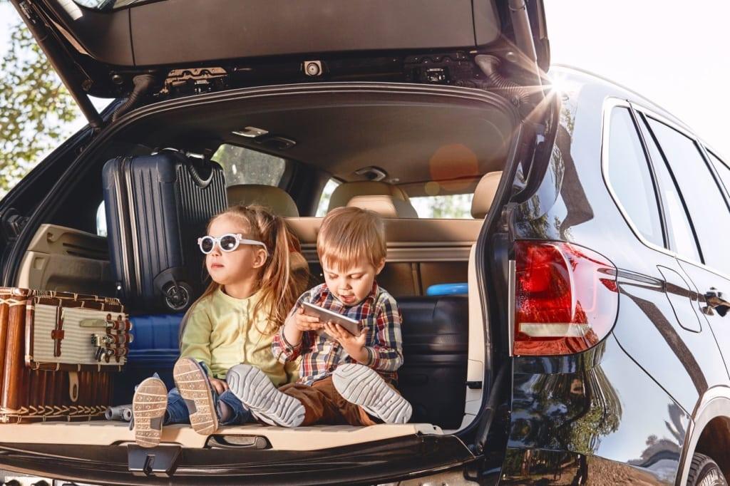 Kinder sitzend im Kofferraum