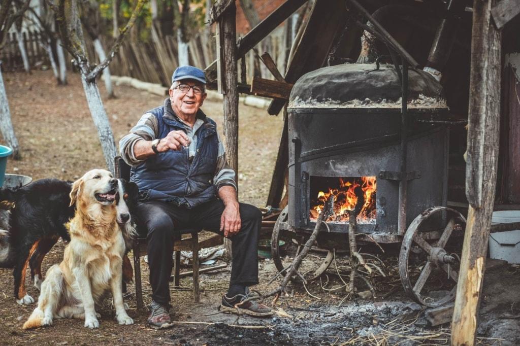 Mann mit Hunden Schnaps brennen