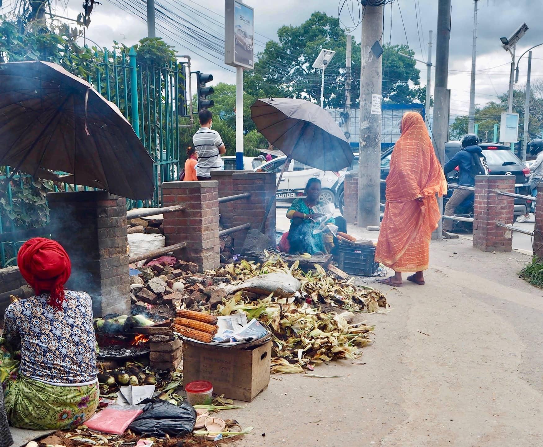 Frauen und Männer verkaufen gegrillte Maiskolben an Straßenrand in Kathmandu, Nepal