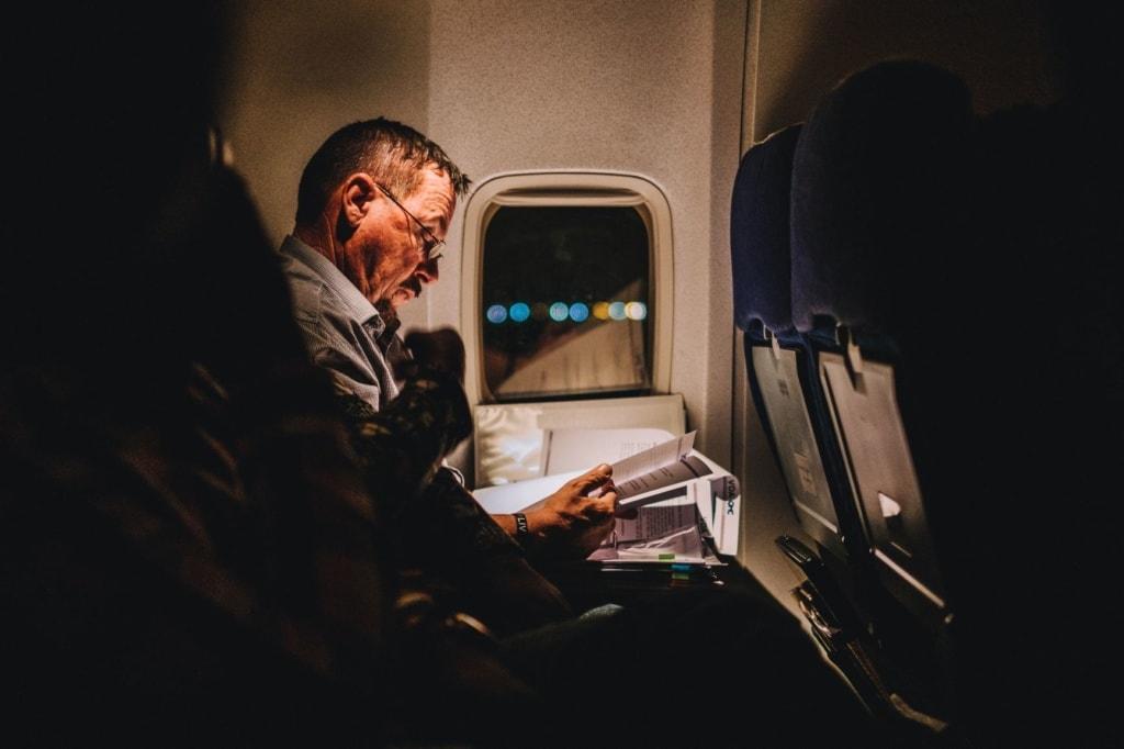 Passagier im Flugzeug, der Dokumente liest
