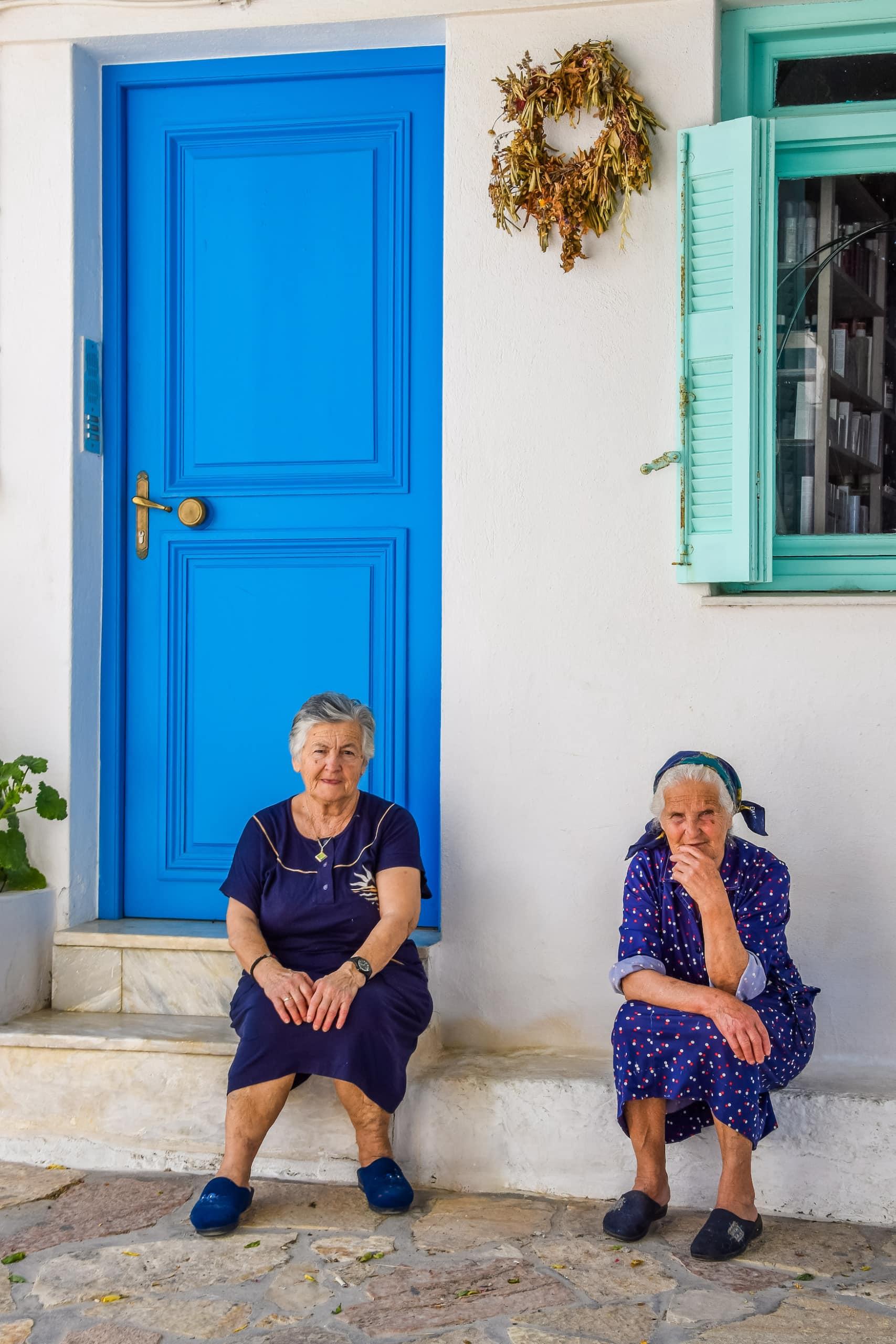 Zwei ältere Damen sitzen vor blauer Haustür auf einer griechischen Insel