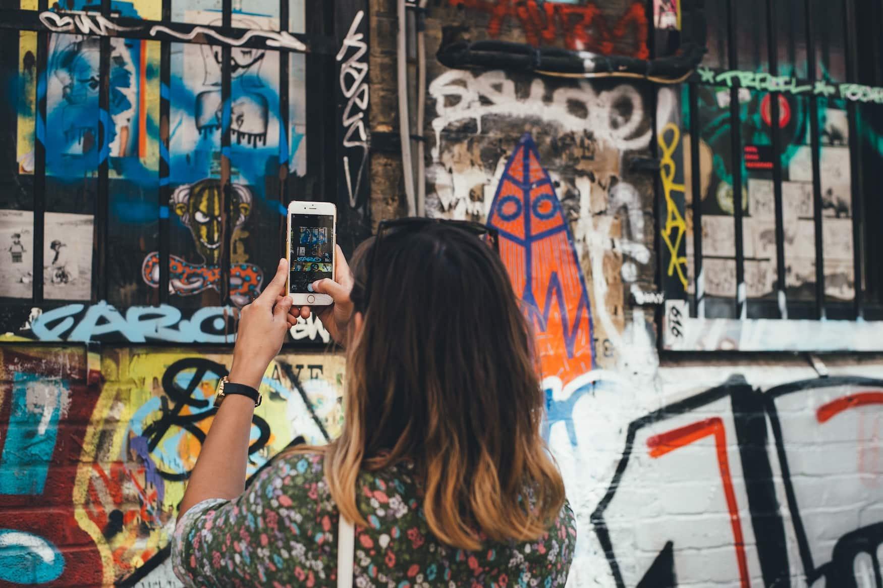 Frau fotografiert Street Art in London