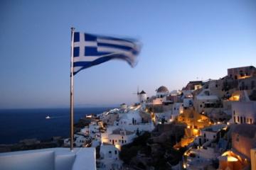 Griechische Flagge weht im Wind vor der Kulisse einer griechischen Insel bei Nacht
