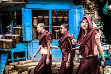 junge männer laufen straße entlang eines shops in kathmandu