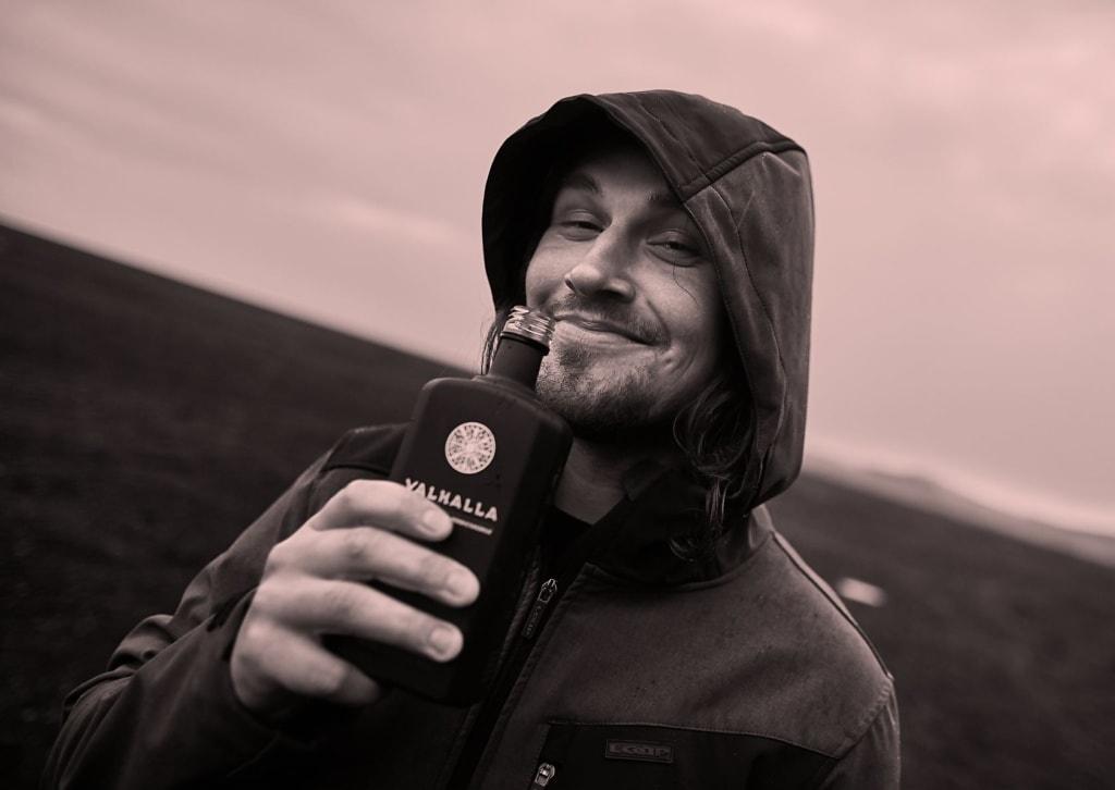 Mann hält Flasche Likör vors Gesicht