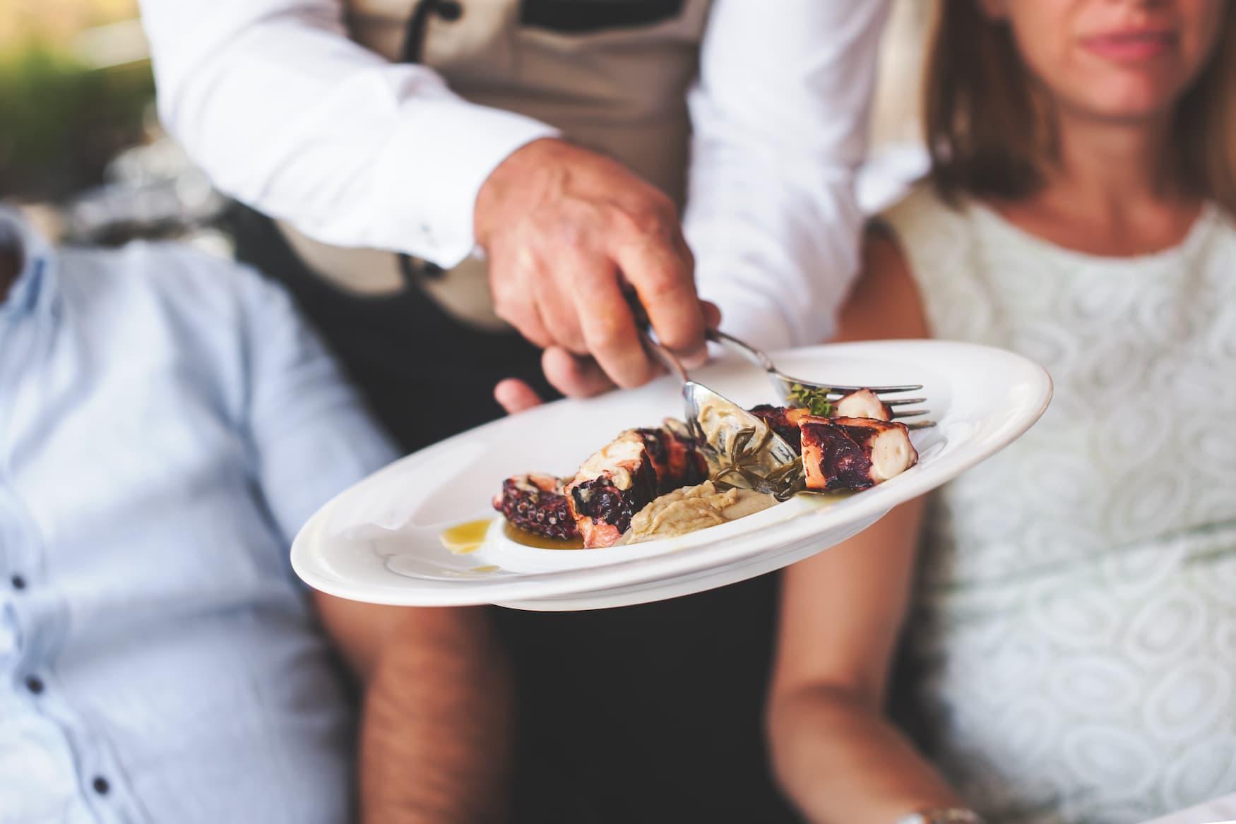 Kellner räumt in Restaurant Teller vom Tisch