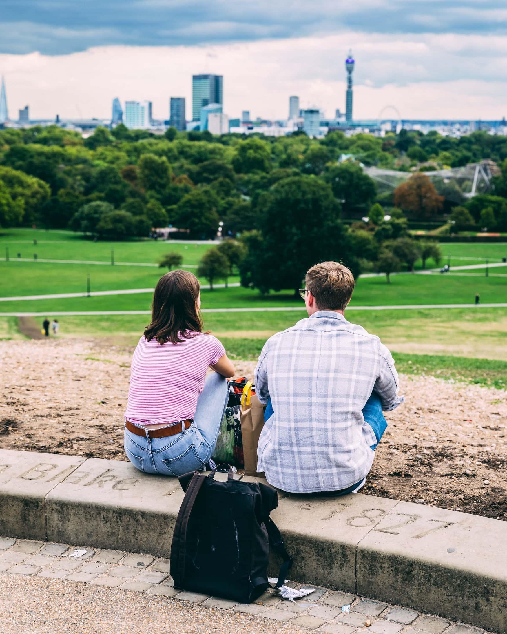 Junges Paar sitzt auf Mauer in Park und guckt auf die SKylien von London
