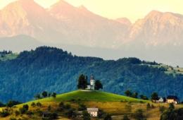 Kirche auf Hügel, im Hintergrund Berge, Slowenien