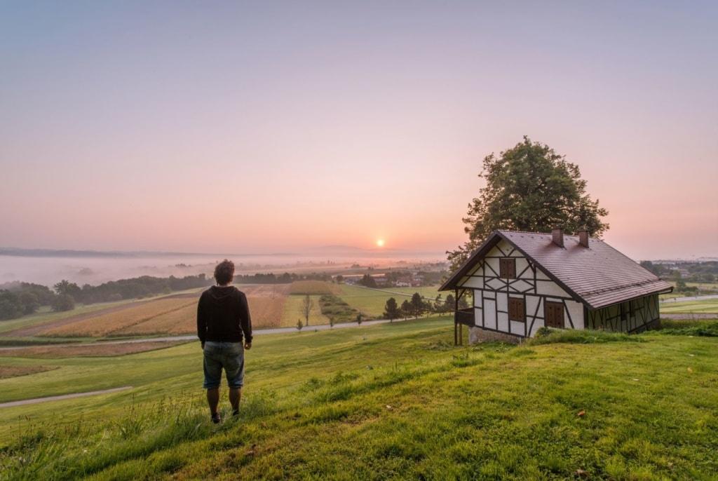 Mann steht auf Hügel und beobachtet Sonnenaufgang