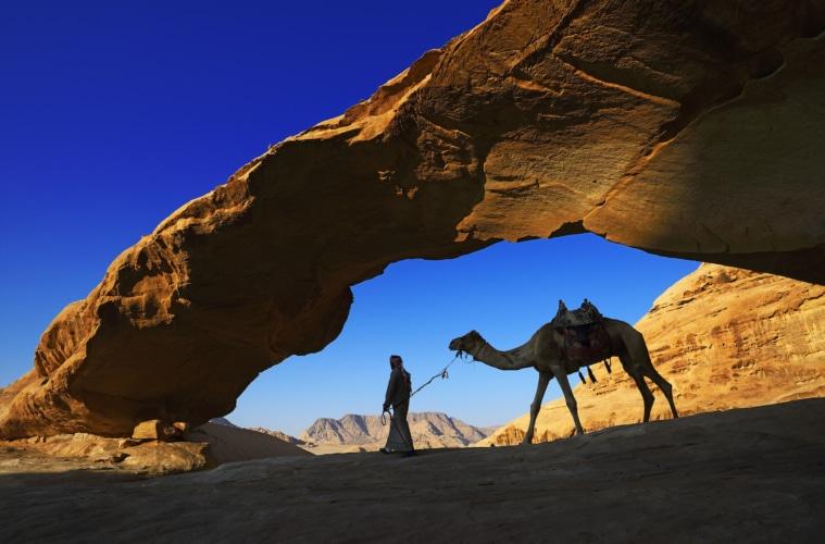 """Ein Beduin reitet sein Kamel durch den Steinbogen """"Al Kharza"""" im Wadi Rum, Jordanien."""