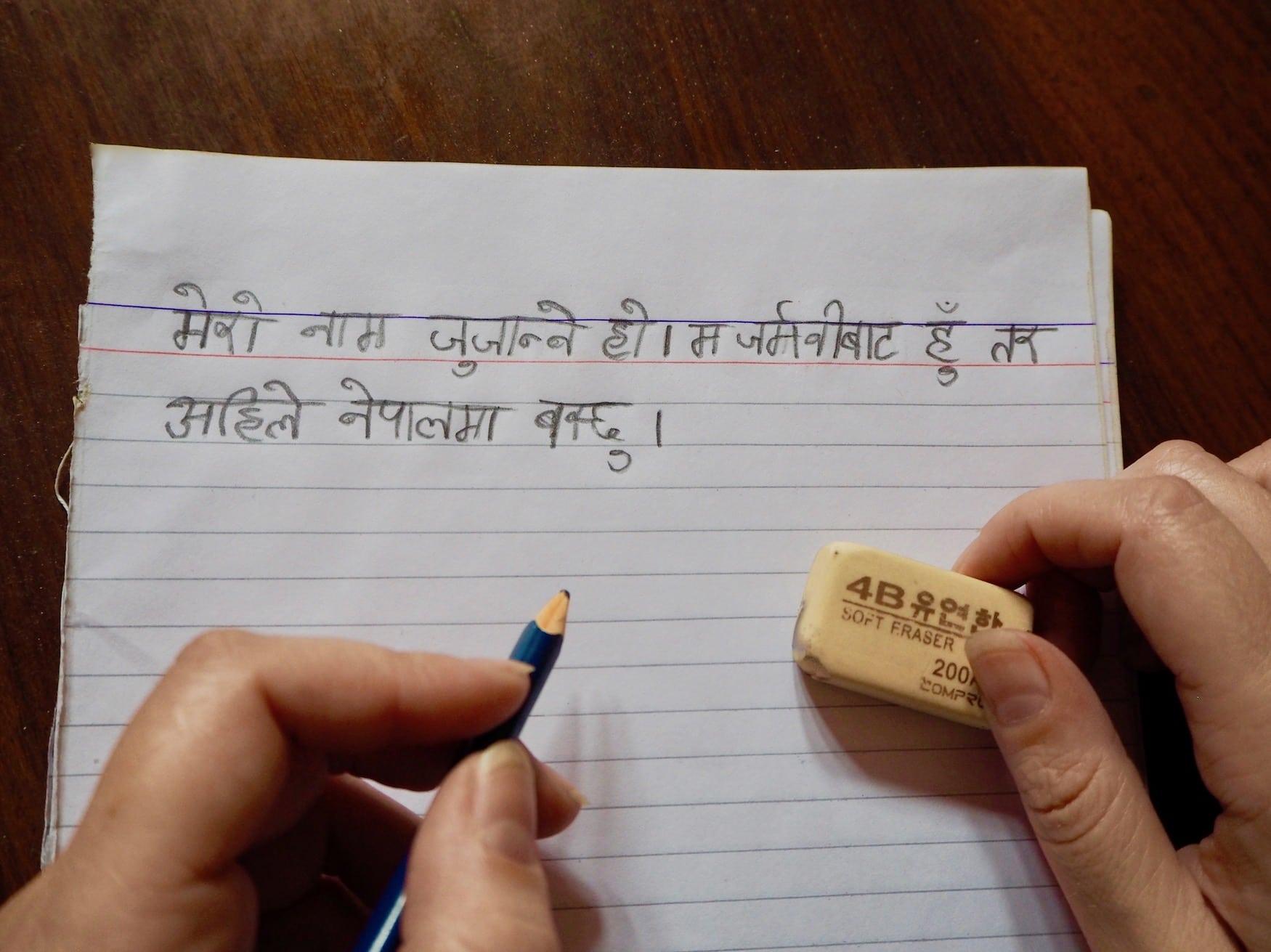 Frau hält Bleistift und Radiergummi und lernt nepalesische Schriftzeichen