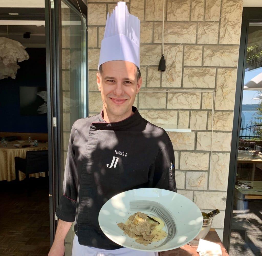 Koch in der Gegend rund um Piran und Portorosž hält Essensteller in Hand