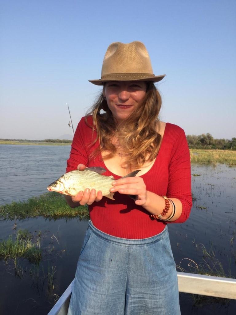Autorin Marie zeigt stolz ihren Fisch, den sie auf dem Sambesi geangelt hat.