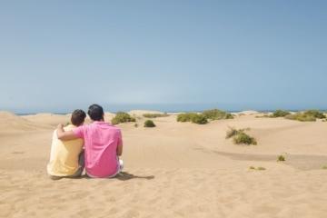 Schwules Paar sitzt in den Dünen auf Gran Canaria
