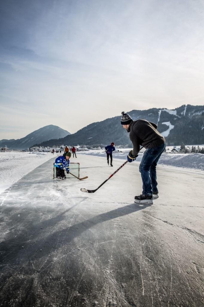 Vater und Sohn beim Eishockey auf einem gefrorenen See in Kärnten