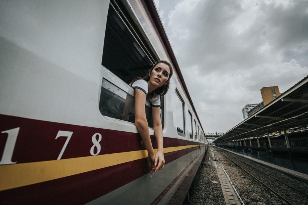 Junge Frau lehnt sich aus Zugfenster in Bangkok, Thailand