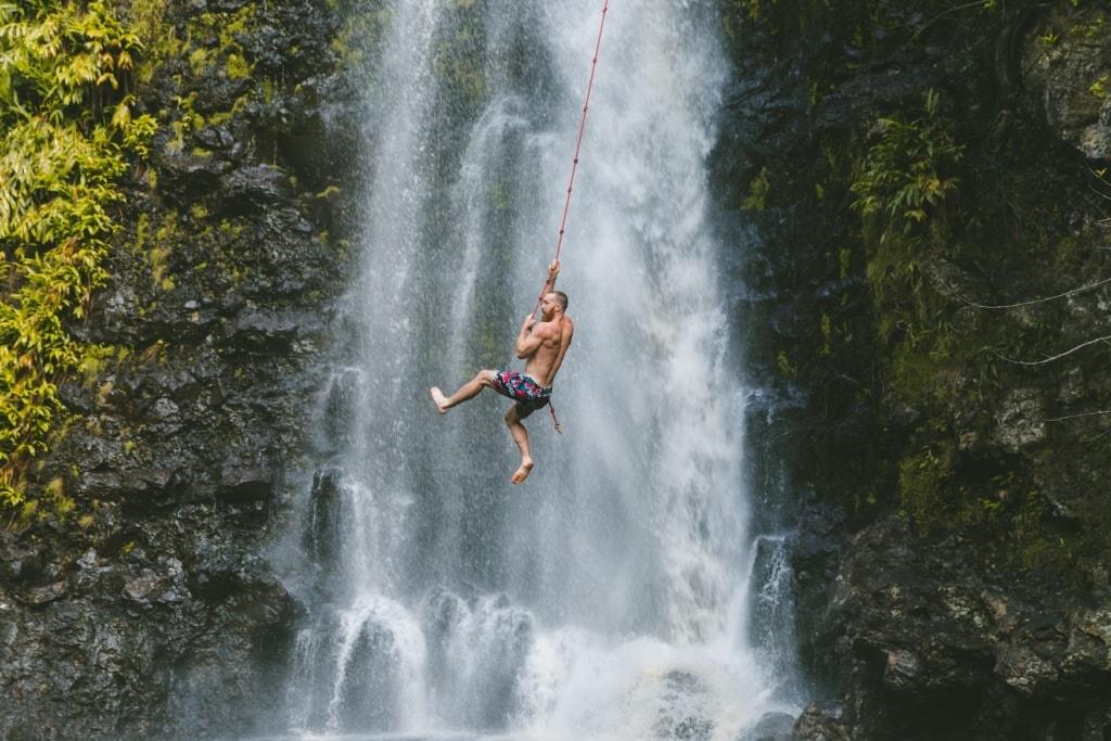 Mann schwingt auf Liane vor Wasserfall