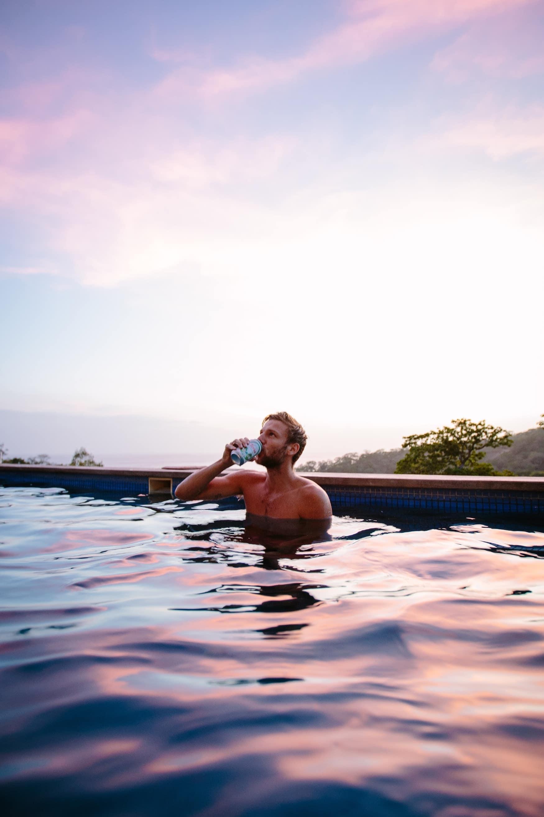 Mann sitzt bei Sonnenuntergang in Pool und trinkt Bier