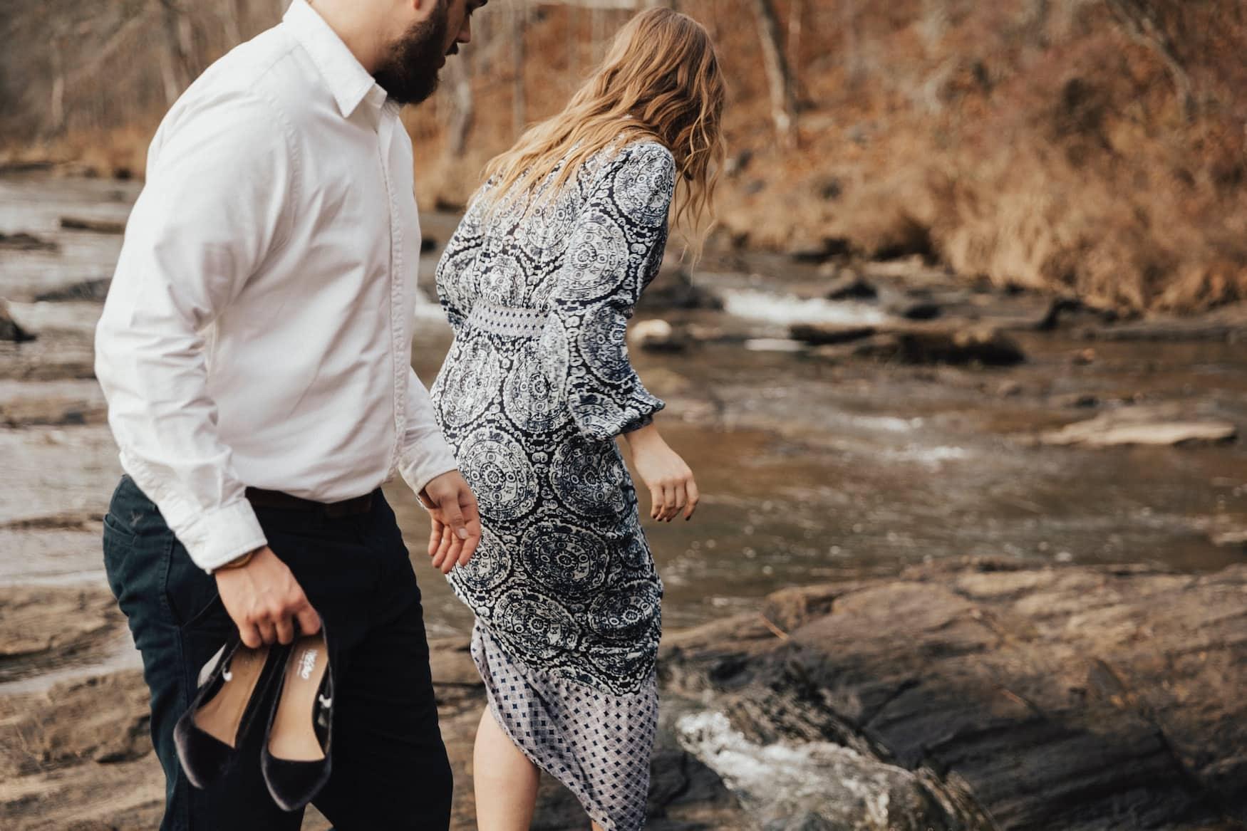 Mann und Frau in schicken Klamotten laufen durch Wald