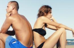 Mann und Frau sitzen am Strand und streiten sich