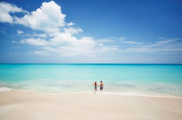 Paar auf Antigua läuft vom Strand ins Meer