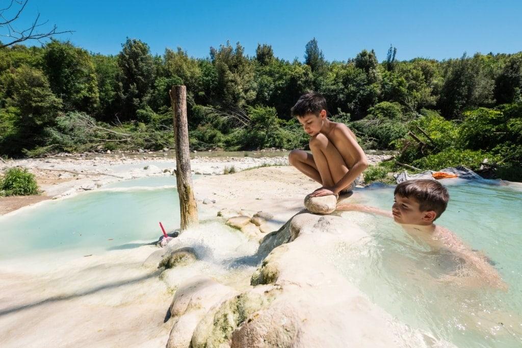 Zwei Jungen baden in der Therme Bagni di Petriolo in der Toskana