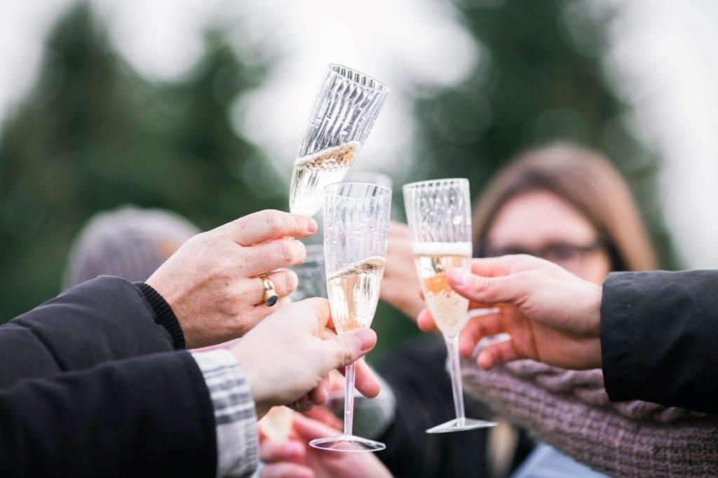 Mehrere Personen stoßen mit Gläsern Champagner an