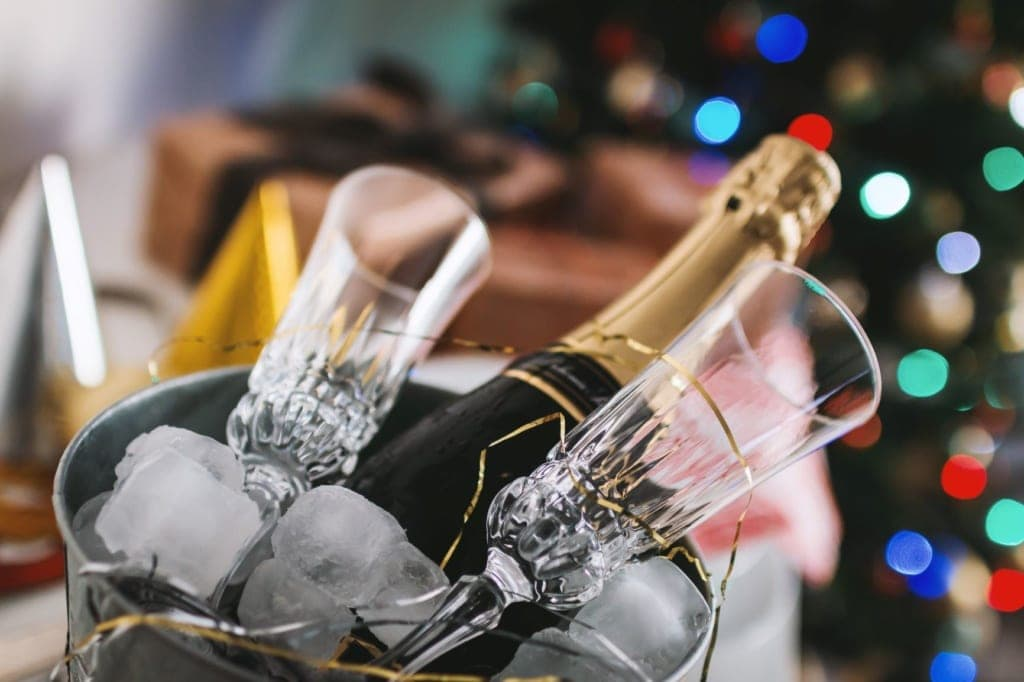 Flasche Champagner und Gläser in einem mit Eiswürfel befüllten Kübel