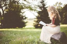 Frau mit blonden Haaren liest Buch auf Wiese