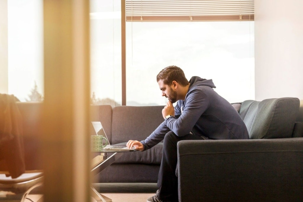 Mann sitzt auf Sofa und schaut in Laptop-Bildschirm