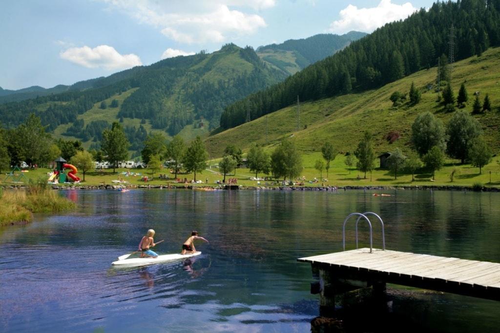 Kinder paddeln auf einem See im Sportcamp Woferlgut