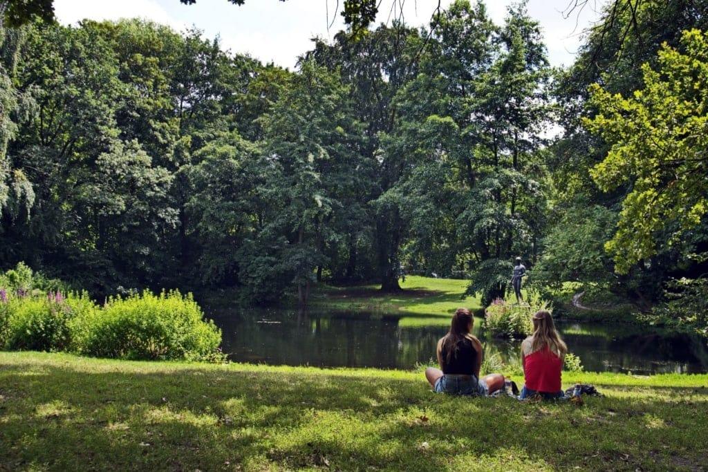 Zwei Frauen sitzen im Berliner Tiergarten am See