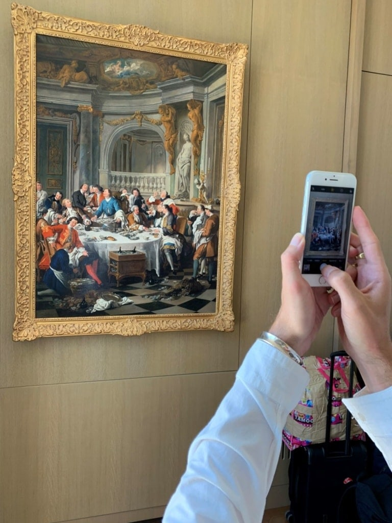 Frau macht Foto mit Handy von einem alten Gemälde